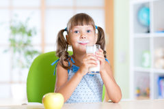 Bambina che mangia prima colazione: bere un vetro di immagini stock libere da diritti