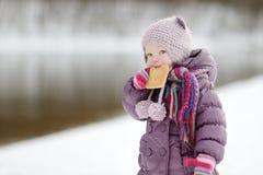 Bambina che mangia un biscotto il giorno di inverno Fotografia Stock