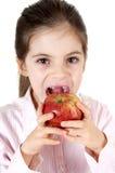 Bambina che mangia una mela Stockfoto