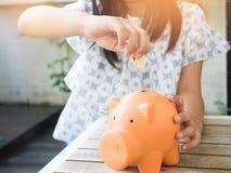 Bambina che mette moneta nel porcellino salvadanaio per il risparmio con il mucchio di Fotografia Stock