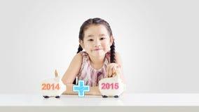 Bambina che mette soldi su un porcellino salvadanaio con un nuovo anno 2015 Immagini Stock Libere da Diritti