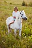 Bambina che monta un cavallo immagine stock libera da diritti