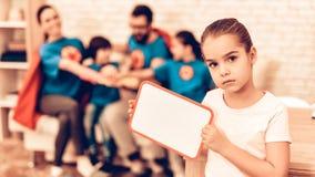 Bambina che mostra bordo in bianco vicino alla famiglia sveglia fotografia stock libera da diritti