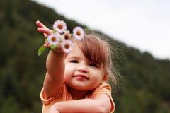 Bambina che mostra i Wildflowers Fotografie Stock