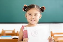 bambina che mostra la carta dell'esame con il più di a nell'aula Fotografie Stock