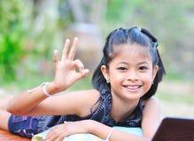 Bambina che mostra okay con la mano fotografie stock