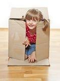 Bambina che nasconde casella di carta interna Immagine Stock