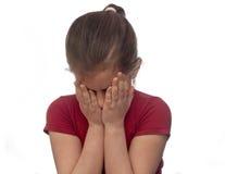 Bambina che nasconde il suo fronte con le sue mani Immagine Stock