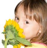 Bambina che odora un girasole Fotografie Stock