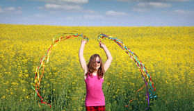 bambina che ondeggia con i nastri variopinti sul campo Fotografie Stock Libere da Diritti