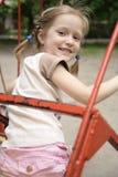 Bambina che oscilla al campo da giuoco Immagini Stock Libere da Diritti
