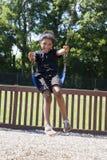 Bambina che oscilla alla sosta Immagine Stock