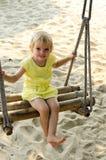 Bambina che oscilla con la spiaggia nei precedenti Fotografia Stock Libera da Diritti