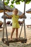 Bambina che oscilla con la spiaggia nei precedenti Immagini Stock