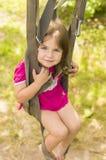 Bambina che oscilla sulle cinghie di un paracadute Immagini Stock