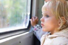 Bambina che osserva attraverso Fotografia Stock