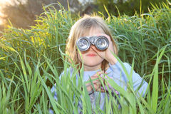 Bambina che osserva tramite il binocolo. Fotografia Stock