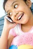 Bambina che per mezzo del cellulare Immagine Stock