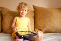 Bambina che per mezzo del computer della compressa Fotografie Stock Libere da Diritti