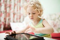 Bambina che per mezzo del computer della compressa Immagine Stock