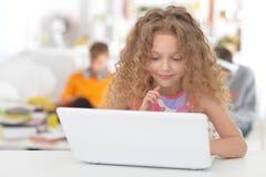Bambina che per mezzo del computer portatile Fotografie Stock