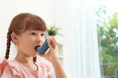 Bambina che per mezzo dell'inalatore di asma immagine stock
