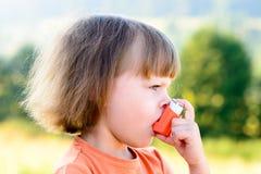 Bambina che per mezzo dell'inalatore un giorno soleggiato Fotografie Stock