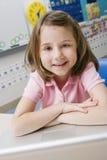 Bambina che per mezzo di un computer portatile Fotografia Stock Libera da Diritti