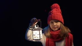 Bambina che porta il cappello tricottato e la sciarpa di inverno che stanno con la lanterna video d archivio