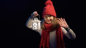 Bambina che porta il cappello tricottato e la sciarpa di inverno che stanno con la lanterna archivi video