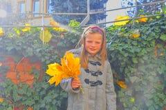 Bambina che porta retro cappotto e che sta davanti al muro di mattoni in autunno Parete dell'edera in autunno Concetto di autunno immagine stock libera da diritti