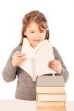 Bambina che porta un uniforme scolastico che legge un libro Fotografia Stock