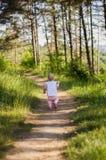 Bambina che porta vestito rosa che fa una passeggiata tutto il da solo in un parco o in una foresta Immagini Stock Libere da Diritti