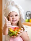 Bambina che prepara alimento sano e mostra Fotografie Stock
