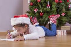 Bambina che prepara Santa Letter Lei che dipinge i regali s immagini stock libere da diritti