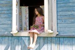Bambina che prevede qualcuno che si siede sulla finestra della casa di campagna Immagine Stock