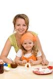 Bambina che produce i biscotti con la sua madre Immagini Stock