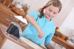 Bambina che produce i pancake Fotografia Stock