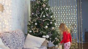 Bambina che prova ad appendere un giocattolo dell'albero di Natale stock footage