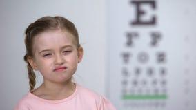 Bambina che prova a leggere le lettere dal grafico di occhio, sistema diagnostico della miopia archivi video