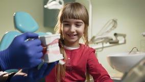 Bambina che pulisce i denti di plastica nel gabinetto del dentista stock footage