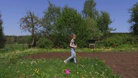 Bambina che raccoglie i fiori in prato
