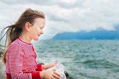 Bambina che riposa dal lago un giorno molto ventoso fotografie stock
