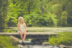 Bambina che riposa sul ponte di legno di estate Fotografie Stock
