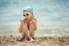 Bambina che riposa sulla spiaggia Fotografie Stock Libere da Diritti
