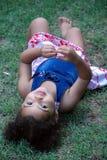 Bambina che risiede nell'erba fotografie stock libere da diritti