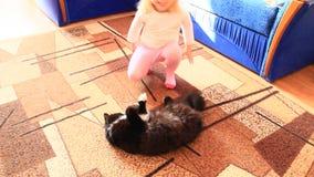 Bambina che scherza e che salta attraverso il gatto Giochi puerili stock footage