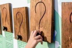 Bambina che scopre che cosa è nell'ambito del punto interrogativo s di legno Immagini Stock Libere da Diritti