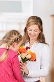 Bambina che sente l'odore di un fiore Fotografia Stock
