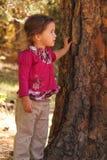 Bambina che si appoggia contro l'albero Fotografie Stock